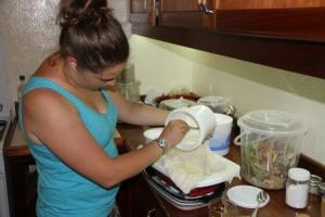 Pouring the cultured yogurt into the cheese cloth so it can drain