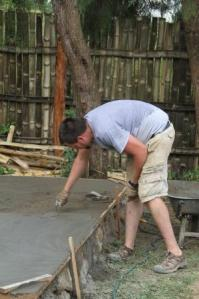 Cement powder is sprinkled over concrete and then smoothed using a trowel to create a smooth surface